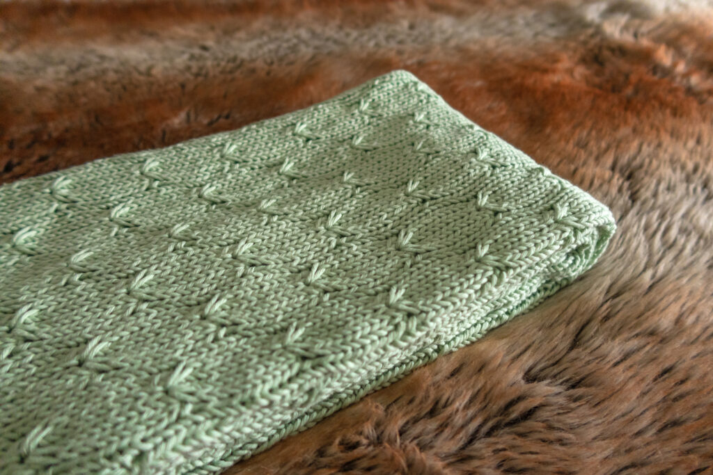A green knitted baby blanket pattern